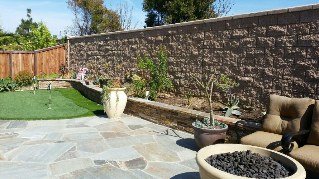 backyard with retaining wall, artificial grass, a fire bowl, and paver patio